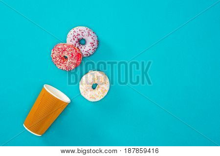 Overhead View Of Scattered Donuts With Various Glaze. Sweet Donuts Isolated On Blue. Sweet Backgroun
