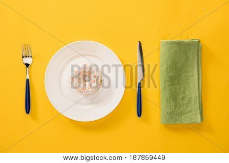 Overhead View Of Donut With Sweet Glaze In Plate And Green Napkin Isolated On Yellow. Background In