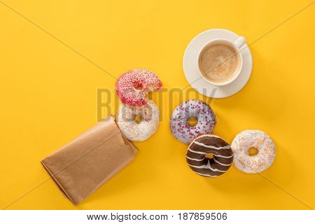 Top View Of Cup Of Coffee And Several Donuts Scattered On Yellow Surface. Donuts Isolated On Yellow