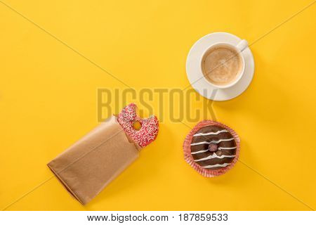 Top View Of Cup Of Coffee With Donuts On Yellow Surface. Donuts And Coffee Background