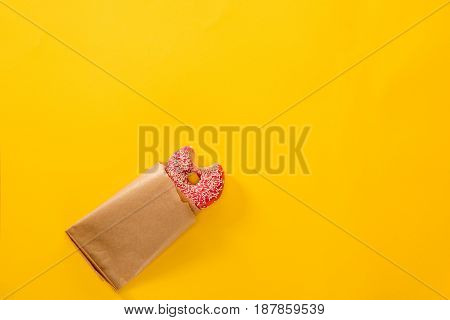 Top View Of Bitten Doughnut In Pink Icing With Paper Bag Isolated On Yellow. Tasty Donut Background