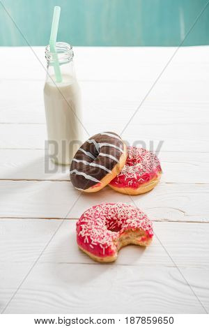 High Angle View Of Milkshake In Glass Bottle With Sweet Donuts On The Table