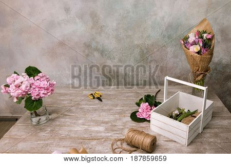 Workplace with flowers, bouquet and rope . Floristry workshop wooden table with decor. Decorative artwork from spring flower