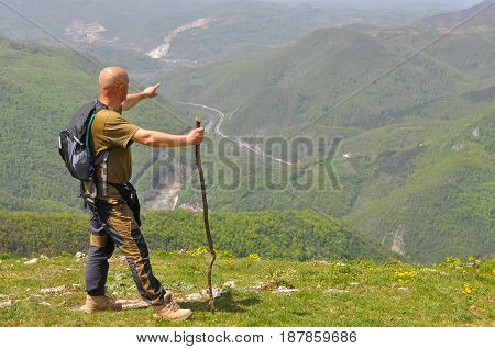Hiker with backpack relies on a stick and pointing to the direction of the valley. Man on top of the mountain look at the valley below