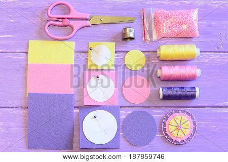 Cute flower made of felt and beads, colored felt circles and sheets, scissors, paper templates, thread spools, needle, pink beads on a wooden table. Sewing instruction. Teach children to sew. Top view