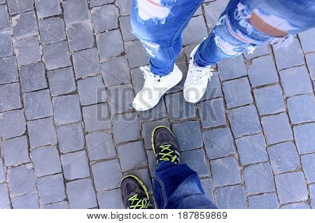 The legs of a guy and a girl in sneakers stand on a stone block the top view.