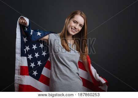 Hold it proud. Emotional magnificent wonderful girl working on patriotic photoshoot and posing for a photographer while standing isolated on grey background