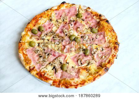 Pizza Margherita on white tablecloth closeup shot