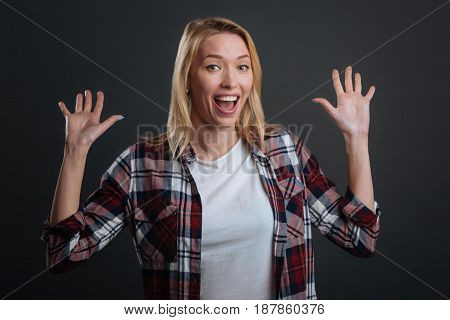 What a surprise. Expressive gorgeous young lady throwing her hands up in excitement while being very emotional and standing isolated on grey background