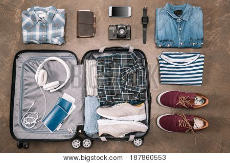 Top View Of An Essential Vacation Items In Open Luggage With Digital Devices On Wooden Background