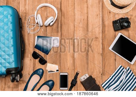 Planning for trip set of travel accessory on wooden floor. Flat lay with baggage passports digital gadgets and clothes.
