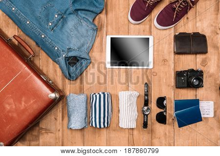 Flay lay of planning of business trip concept with suitcase clothes gadgets passport and tickets on wooden floor.