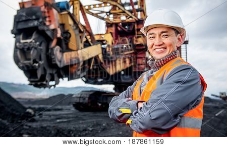 coal mining worker with rotary excavator on the background