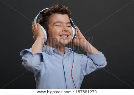 Cool sound. Adorable emotional cute boy wearing the headphones and listening to music while standing isolated on grey background