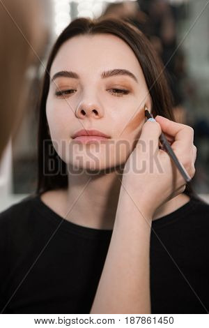 Beautician making face contouring with makeup brush. Modern trend in visage