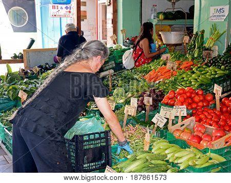 HERAKLION, CRETE - SEPTEMBER 19, 2016 - Cretan stallholder sorting vegetables on a market stall in the city centre Heraklion Crete Greece Europe, September 19, 2016.