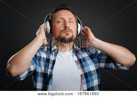 Perfect playlist. Charming thoughtful young guy enjoying the playlist while using headphones and holding his eyes closed