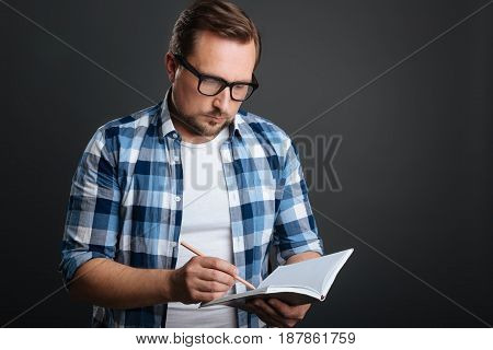 Focused writer. Organized devoted calm guy compiling a schedule while using his journal and a pencil for writing it down
