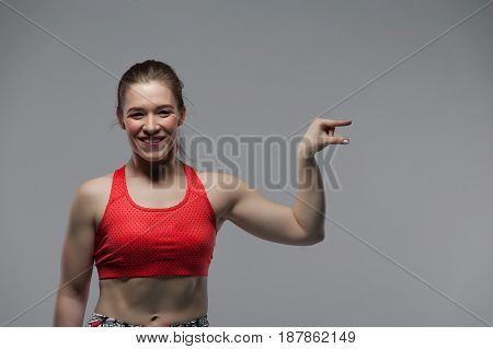 Attractive brunette woman wearing red top looking at camera and posing on white background. Portrait of smiling sport girl pointing finger to copyspace. Fitness motivation concept.