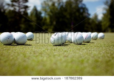 Horizontal outdoors shot of a pile of balls lying on the golf course.
