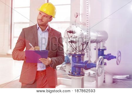 Young male inspector writing on clipboard while looking away in industry