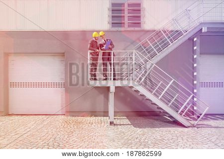Young male engineers with clipboard discussing on stairway