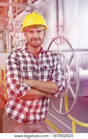 Portrait of worker with arms crossed leaning on large valve in industry