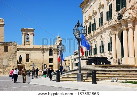 VALLETTA, MALTA - MARCH 30, 2017 - View of the Auberge de Castille in Castille Square with tourists enjoying the setting and Our Lady of the Victories church to the rear Valletta Malta Europe, March 30, 2017.