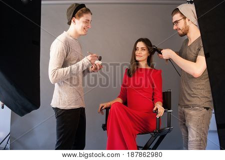 Hairdresser and make-up artist work together in studio . Men doing makeup and hairstyle for woman. Creative team make commercials. Photo school, lookbook, fashion backstage concept