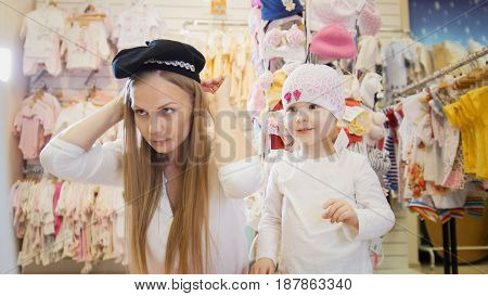 Mom wears a black hat in front of a mirror in a clothing store for children