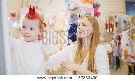A little girl tries on a red rim in the form of a crown in front of a mirror in a clothing store for children