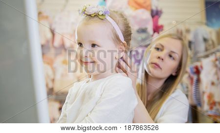 Shopping for kids - Mother clothes daughter accessoriesnear mirror