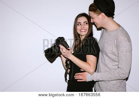 Two young people enjoy with digital camera on white background. Female photographer show to male model photos. Woman and man is happy. Friendship of sexes, lifestyle, couple leisure, hobby concept