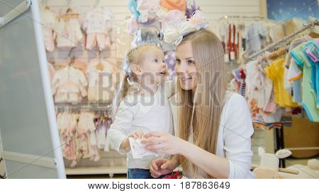 Little girl and her mommy feel happy n the children's clothing store