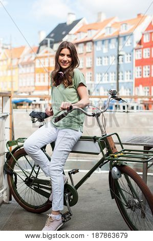 Young happy woman on bicycle looking at camera at the Nyhavn harbor pier in european city Copenhagen, Denmark. Visiting Scandinavia, famous European. poster