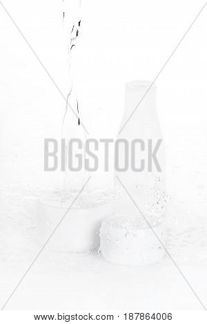 Water Drops Falling On Bottle And Boxes Isolated On White
