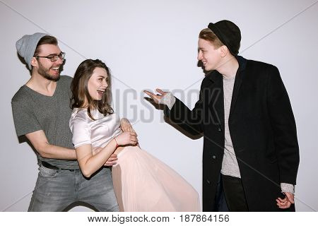Group of friends have fun together at party. Woman and two men in playful mood on white background. Casual youth communicate, laugh and smiles