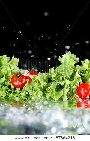Close-up View Of Fresh Ripe Cherry Tomatoes With Lettuce And Water Drops Isolated On Black, Harvest