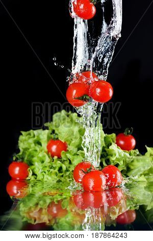 Red Fresh Cherry Tomatoes And Green Lettuce In Water  Isolated On Black, Fresh Vegetables Falling In