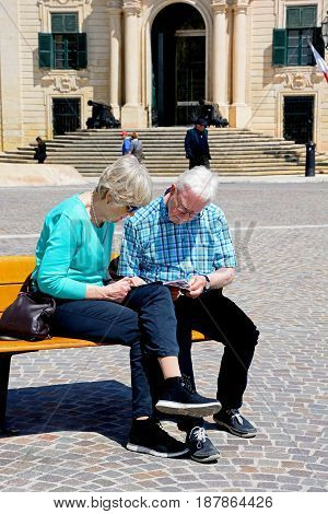 VALLETTA, MALTA - MARCH 30, 2017 - Couple sitting on a bench reading a guide book with the Auberge de Castille to the rear in Castille Square Valletta Malta Europe, March 30, 2017.