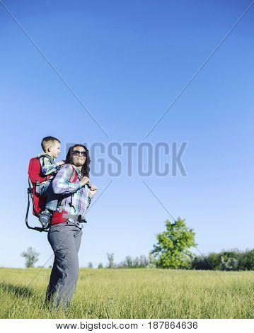 Mother with baby in backpack carrier is hiking in mountains. Tourist is carrying a child on his back on the nature.