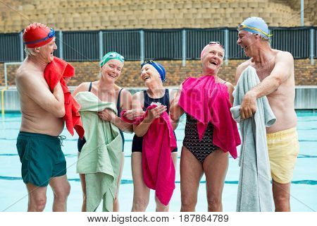Group of happy senior swimmers wiping body with towels at poolside