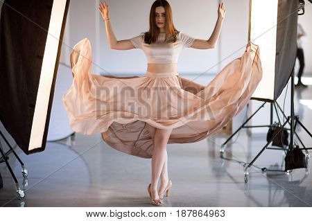 Beautiful model in flying dress posing in studio . Fashion, vogue, glamour, lightness concept. Many professional light equipment around