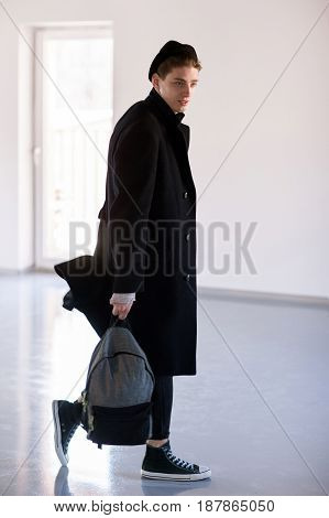 Fashion man with backpack in studio. Guy in casual cloth walks with bag in hands. Professional model on photoshoot