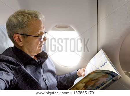 Middle aged caucasian man reading magazine while traveling by plane. Aircraft cabin interior