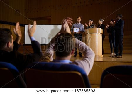 Business executives actively applauding in conference center