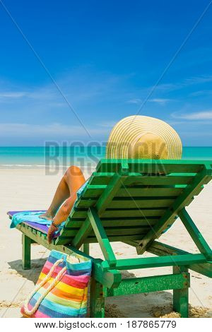 Travel vacation woman relaxing lying down on sun bed sofa lounge chair on holidays.
