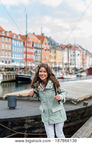 Young tourist woman visiting Scandinavia at Copenhagen, Nyhavn, Denmark. Visiting Scandinavia, famous European destination during fall or spring. Travel and Lifestyle. poster