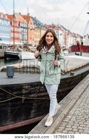 Young tourist woman visiting Scandinavia at Copenhagen, Nyhavn, Denmark. Visiting Scandinavia, famous European destination during fall or spring. Travel and Lifestyle.