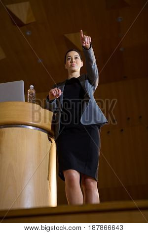 Female business executive pointing while giving a speech at conference center